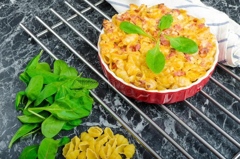 Baked homemade pasta with leeks, bacon and cream. Spinach and fresh tomatoes from the garden stock photo