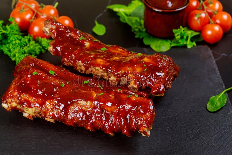 Baked juicy barbecue pork ribs with tomato, sauce and parsley royalty free stock photography