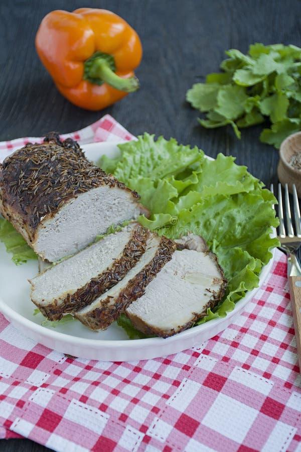 Baked kokade griskött i kryddor som skivades på en vit platta med grön sallad m?rkt tr? f?r bakgrund arkivfoton
