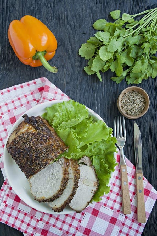 Baked kokade griskött i kryddor som skivades på en vit platta med grön sallad m?rkt tr? f?r bakgrund royaltyfria foton