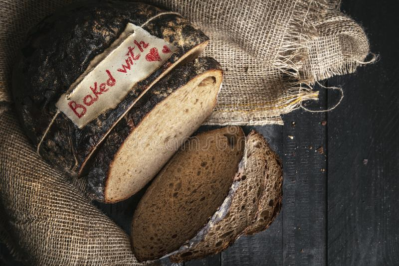 Baked with love tag on a rye bread on a rustic table. Above view of traditional German brown bread royalty free stock photography