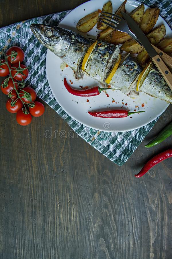Baked mackerel with lemon and baked potatoes on a white plate. Fresh vegetables . Cherry, chili pepper. Cutlery. View from above. royalty free stock images