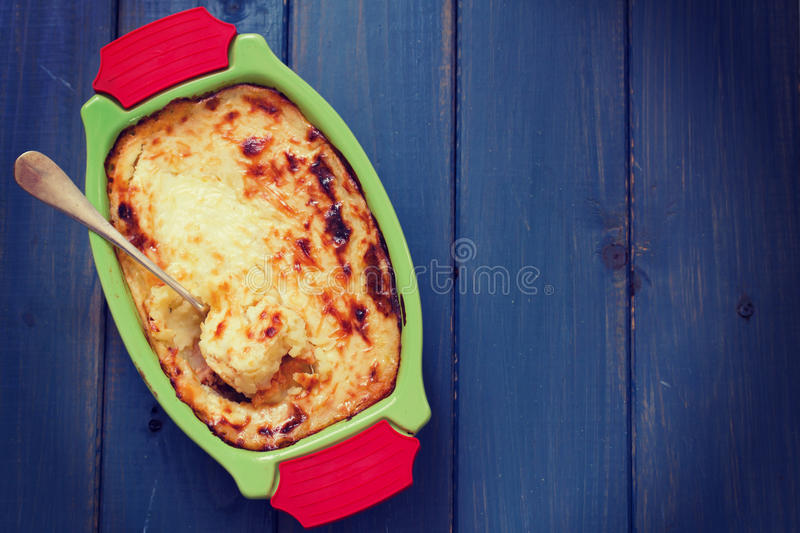 Baked mashed potato with fish in green dish stock images