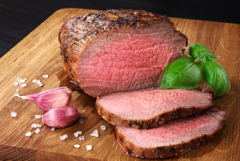 Baked meat, garlic and basil. Roast beef. stock image