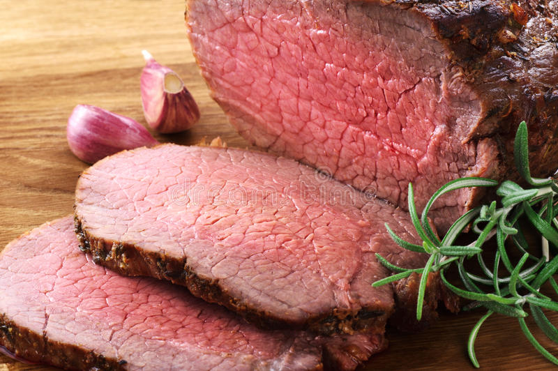 Baked meat, garlic and rosemary. Roast beef. royalty free stock photo