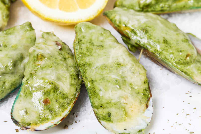 Baked mussels with spinach and parmesan cheese. royalty free stock images