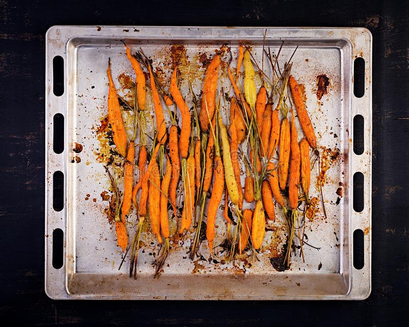 Baked organic carrots with thyme, honey and lemon. Organic vegan food. Top view royalty free stock photo
