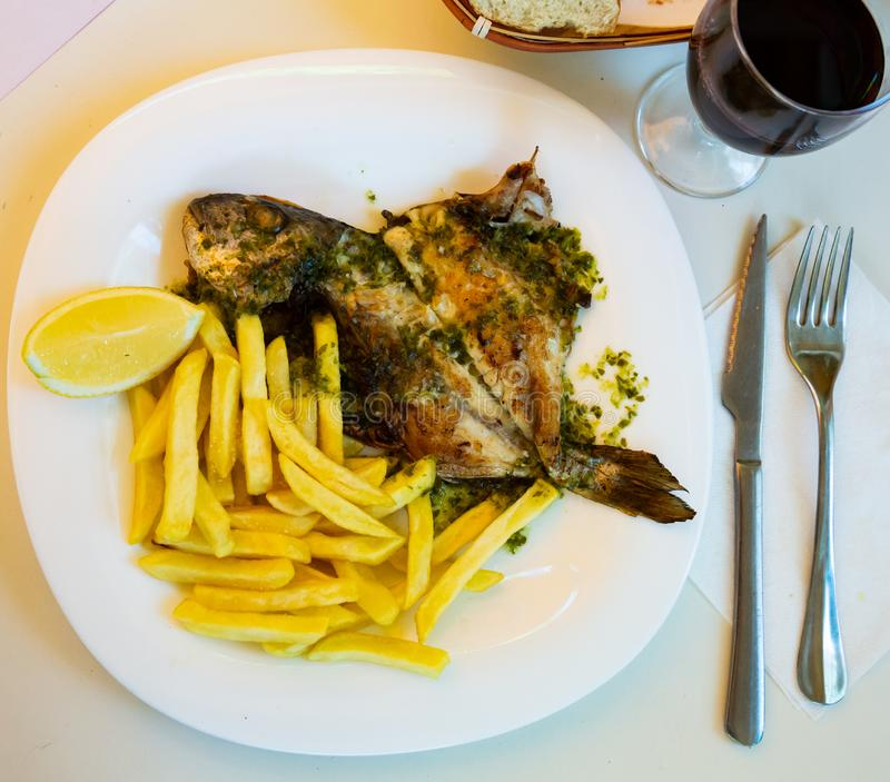 Baked in oven dorado fish with lemon and french fries served. On plate royalty free stock images