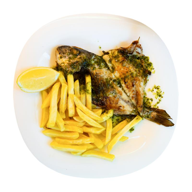 Baked in oven dorado fish with lemon and french fries served. On plate. Isolated over white background royalty free stock photo