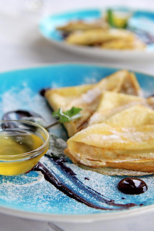 Baked pancakes with mint honey powdered sugar and sauce on blue plate royalty free stock photography