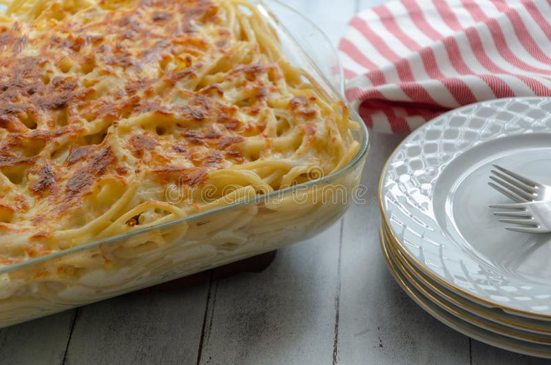 Baked pasta on wooden table. Baked pasta ready meal with spiral pasta, sauce and cheese stock images