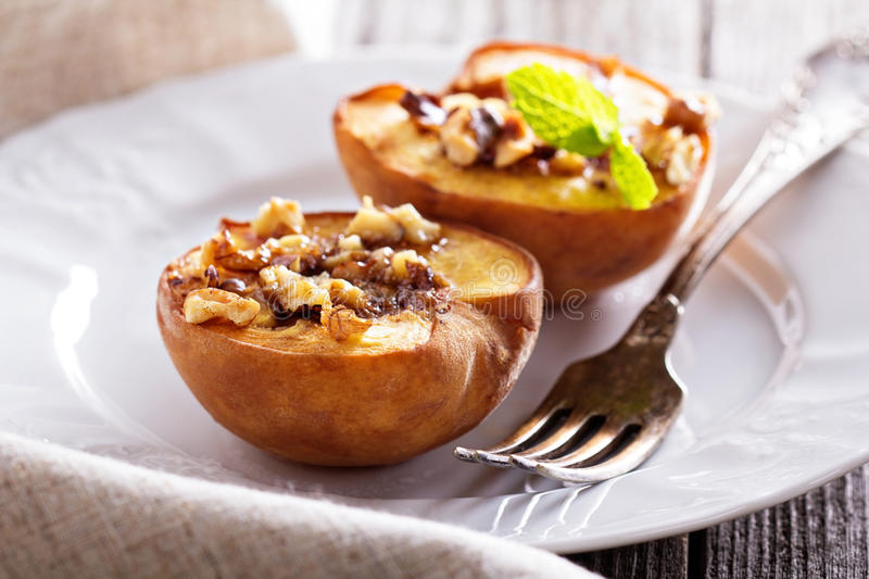 Baked peaches with sugar and nuts royalty free stock image
