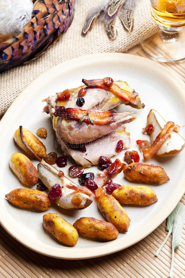 Baked pheasant. With bacon, pear, raisins on brandy royalty free stock photos