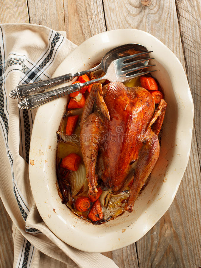Baked pheasant in red wine with carrot and onion. In baking dish stock photo