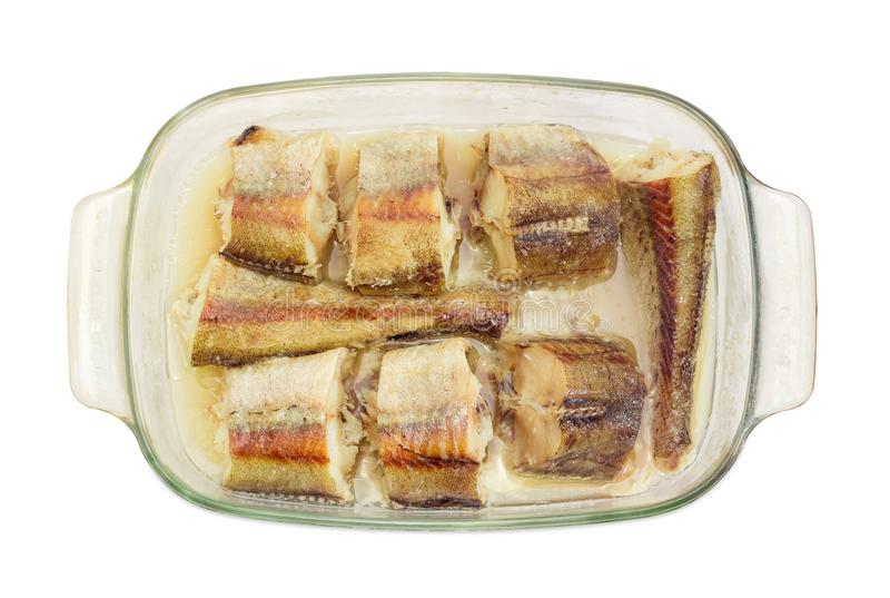 Baked pieces of hake in glass casserole pan closeup stock photography
