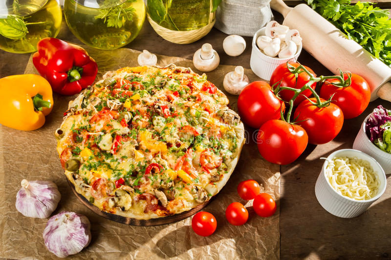 Baked pizza and fresh ingredients stock images