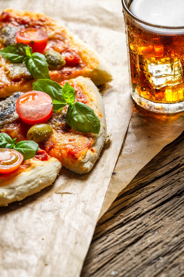 Baked pizza served with a cold drink with copy space place royalty free stock photo