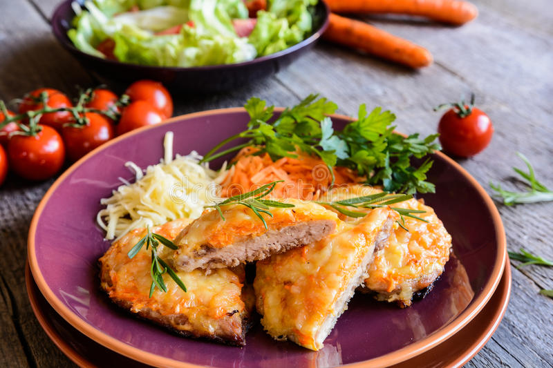 Baked pork cutlets coated in cheese and carrot with salad stock photos