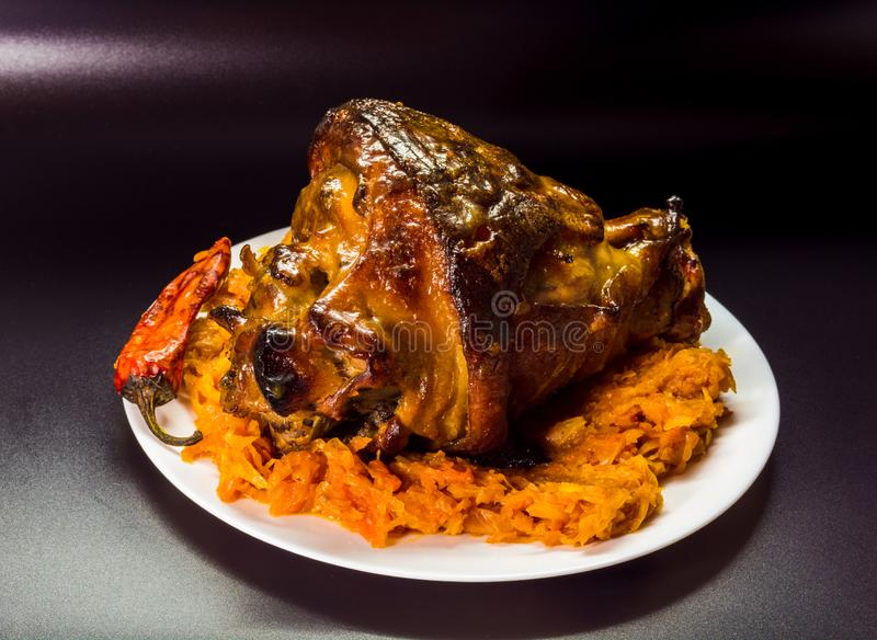 Baked pork leg. Delicious food on a black background stock image