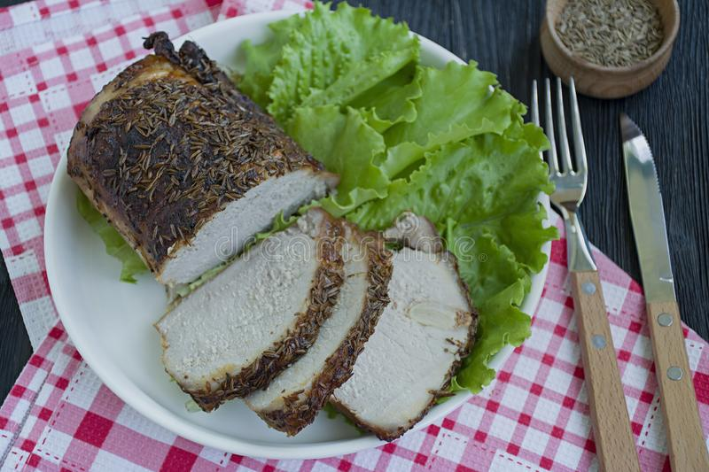 Baked pork tenderloin in spices sliced on a white plate with green salad. Dark wooden background stock images