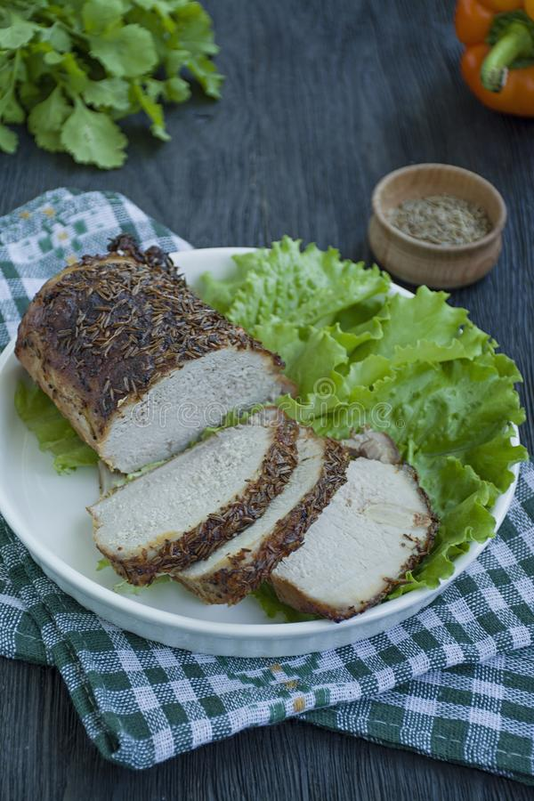 Baked pork tenderloin in spices sliced on a white plate with green salad. Dark wooden background stock photography