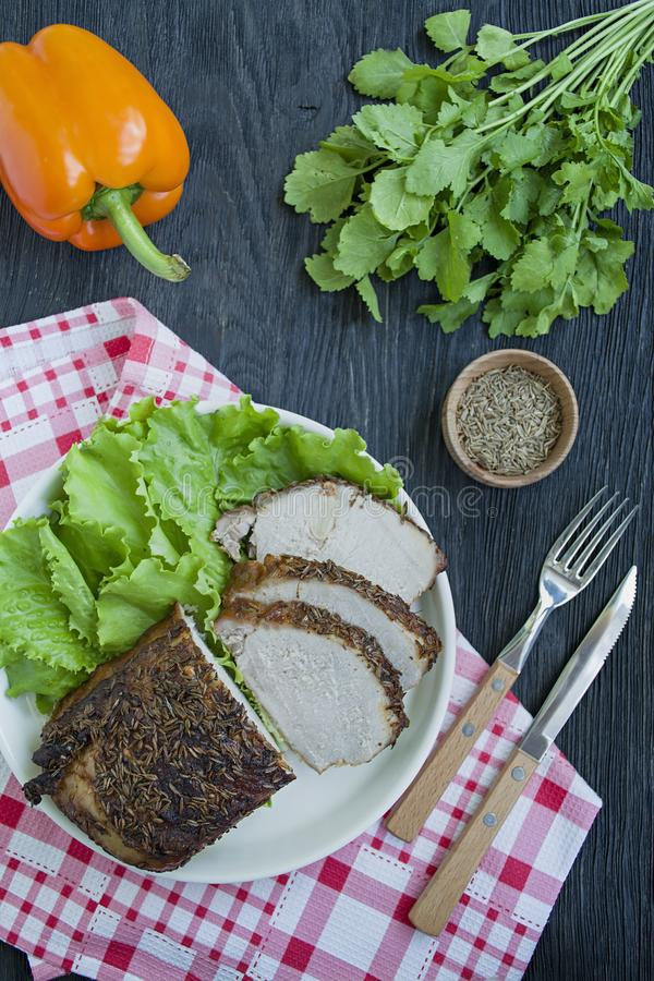 Baked pork tenderloin in spices sliced on a white plate with green salad. Dark wooden background stock photos