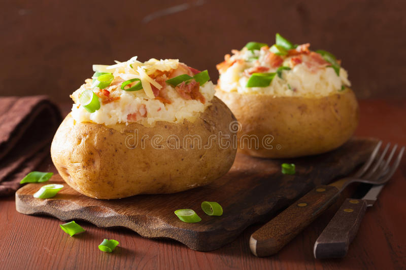 Baked potato in jacket with bacon and cheese. Baked potato in jacket with bacon cheese royalty free stock photos