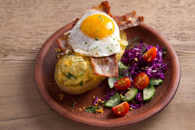 Baked potato in jacket loaded with cheese and topped with bacon and fried egg on plate with vegetables. Stuffed potato with toppin royalty free stock photography