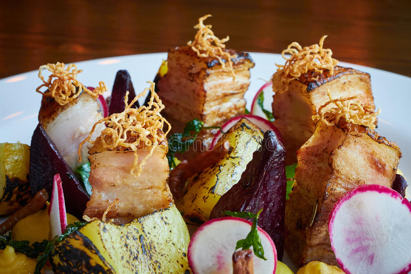 Baked potato slices and beets with vegetables and roast pork bacon close up stock photography