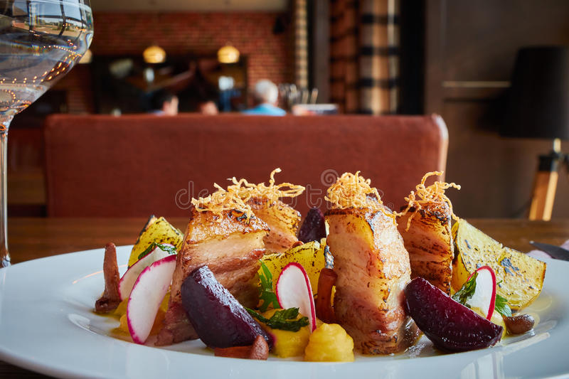 Baked potato slices and beets with vegetables and roast pork bacon on dark wooden table served in restaurant interior royalty free stock photo