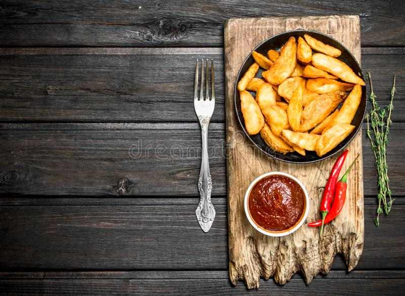 Baked potato slices with tomato sauce and hot chili peppers royalty free stock images
