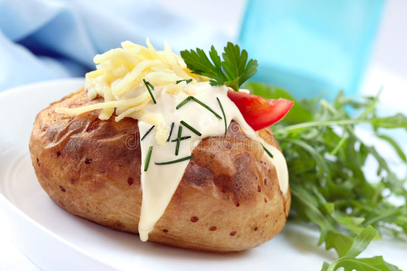 Baked Potato with Sour Cream Grated Cheese Chives and Salad royalty free stock photo