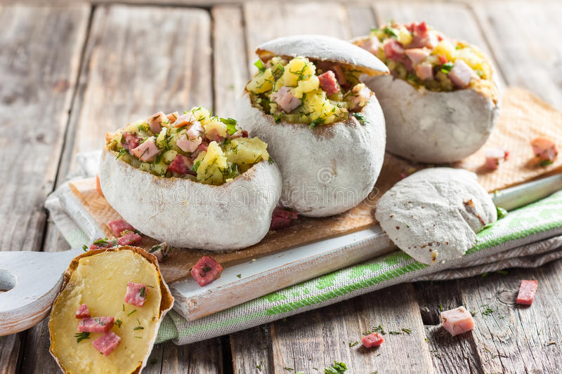 Baked potato stuffed with ham stock images