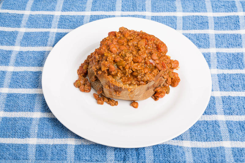 Baked Potato Topped with Spicy Chili. A hot baked potato in white plate smothered in spici chili with beans and meat royalty free stock image