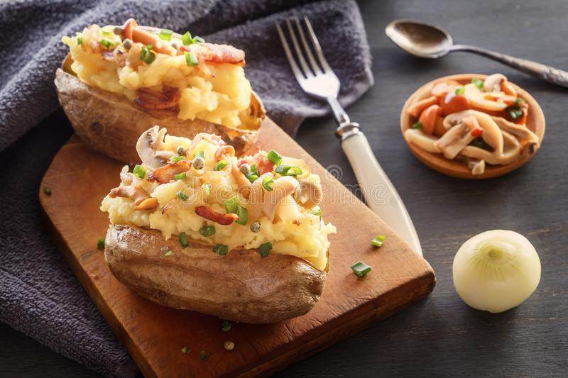 Baked potatoes with bacon and mushrooms in a rustic way on a wooden board. stock photo