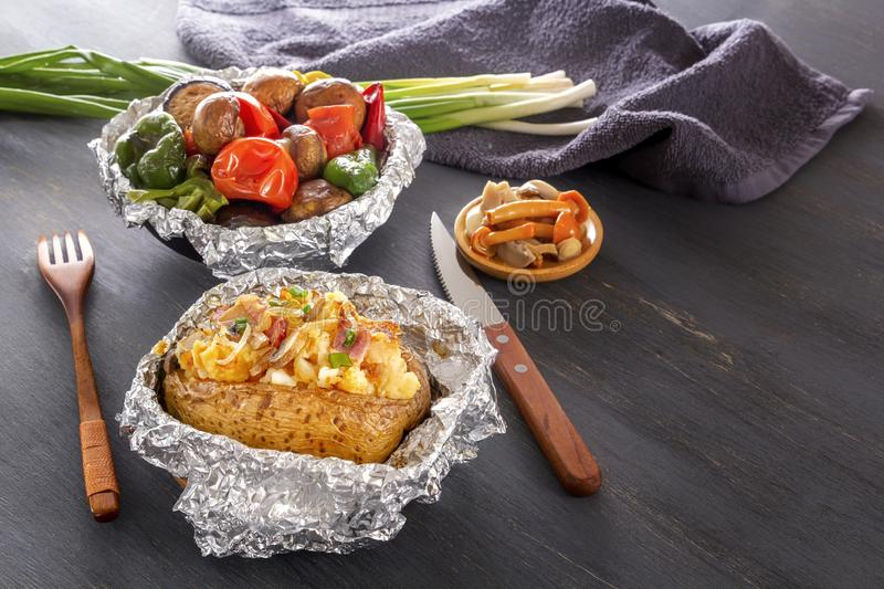 Baked potatoes with bacon, onions and baked vegetables in foil - tomatoes, eggplants, peppers royalty free stock photography