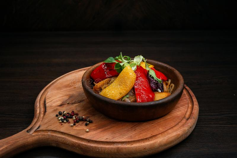Baked potatoes, Bulgarian yellow and red peppers, eggplants on a pot on a wooden table in a restaurant of Georgian cuisine. royalty free stock images
