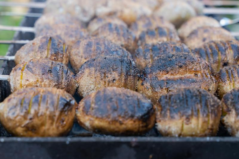 Baked potatoes on the coals on the grill with a Golden crust. food preparation. And cooking, background, black, dinner, fire, heat, hot, outdoors, traditional royalty free stock photos