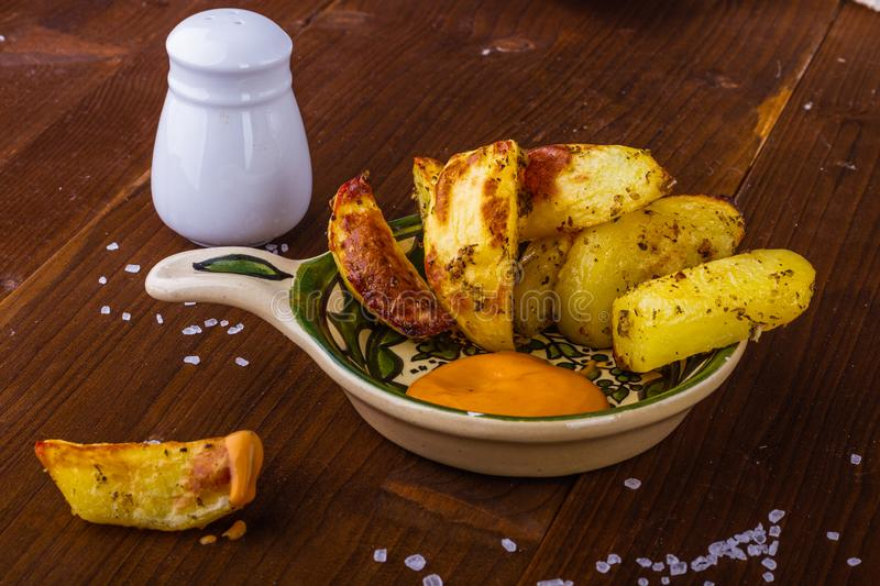 Baked potatoes. Hot fries. French fries with a spicy sauce. Potatoes with herbs. Delicious food. stock photos