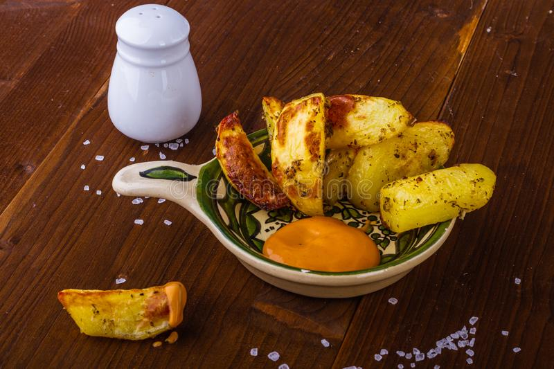 Baked potatoes. Hot fries. French fries with a spicy sauce. Potatoes with herbs. Delicious food. royalty free stock photos