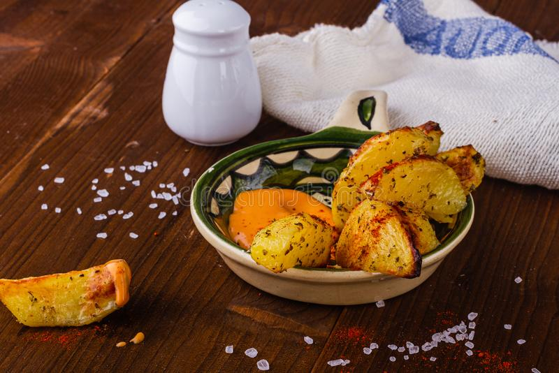 Baked potatoes. Hot fries. French fries with a spicy sauce. Potatoes with herbs. Delicious food. stock image