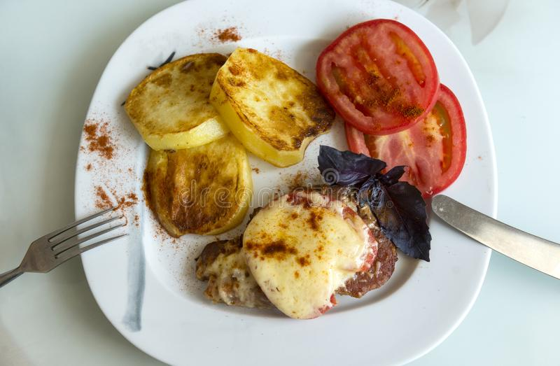 baked potatoes, meat, French pork, sliced tomato on a plate, Basil sprig, cheese, fork, knife, food in a plate on the table royalty free stock photography