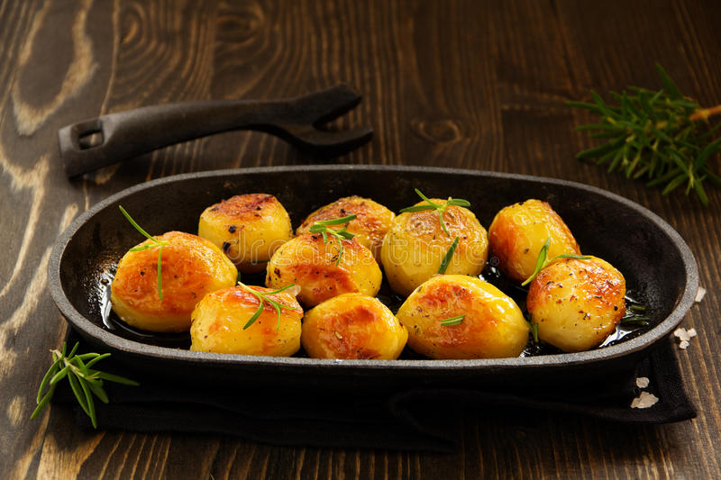 Baked potatoes with rosemary. And dry Provencal herbs stock photo