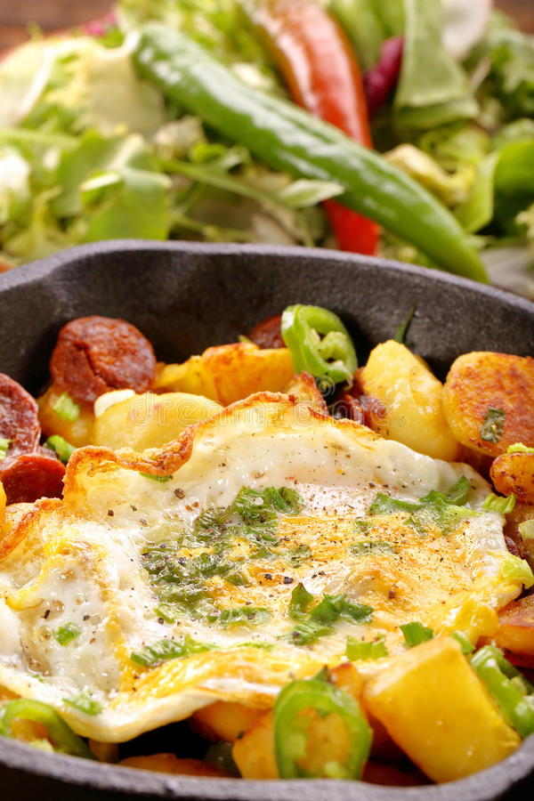 Baked potatoes with sausage chorizo and fried egg on frying pan. Baked potatoes with sausage chorizo fried egg and green chilli peppers on frying pan royalty free stock photo