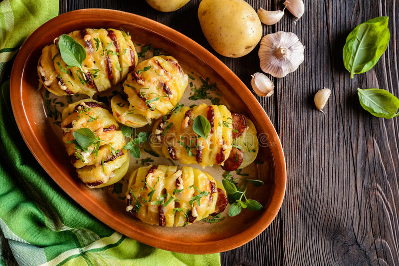 Baked potatoes stuffed with sausage, cheese, garlic and herbs stock photos