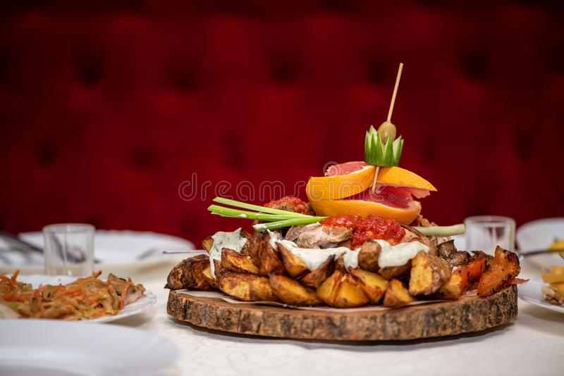 Baked potatoes with vegetables and fruits on a wooden stand, in restaurant, catering royalty free stock photography