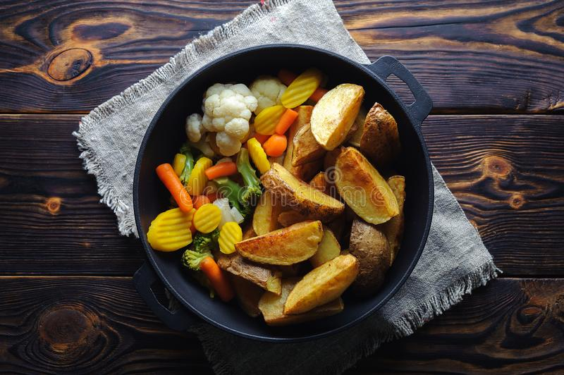 Baked potatoes with vegetables in a pan on a wooden background royalty free stock photography