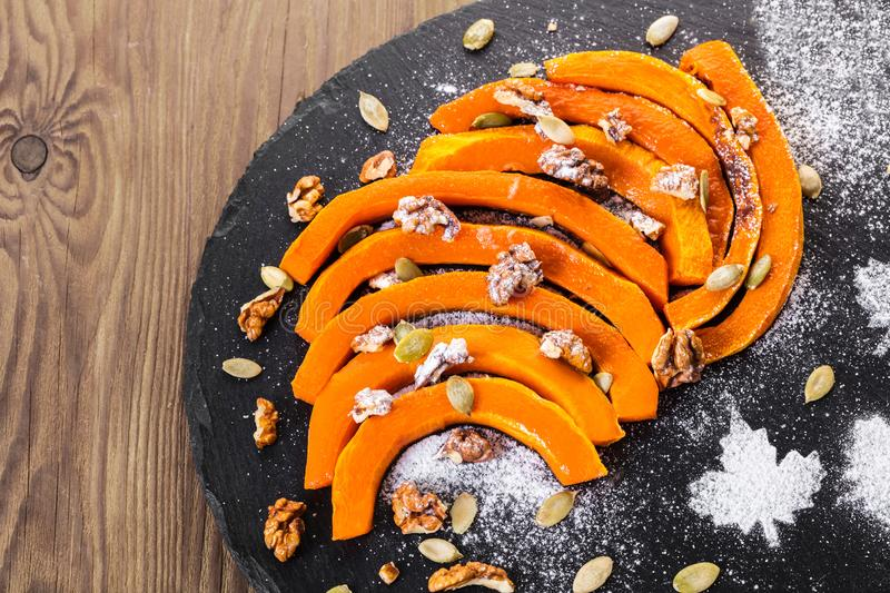Baked pumpkin slices with nuts stock photography