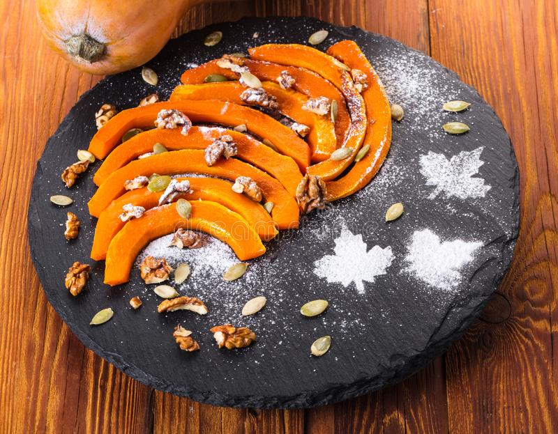 Baked pumpkin slices with nuts stock images