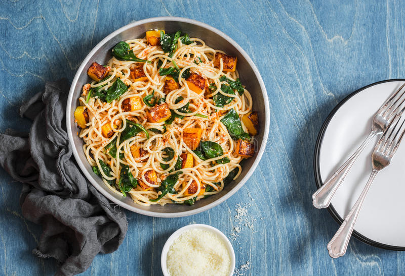 Baked pumpkin and spinach spaghetti in a frying pan on wooden table, top view. Delicious lunch in a mediterranean style. royalty free stock photo